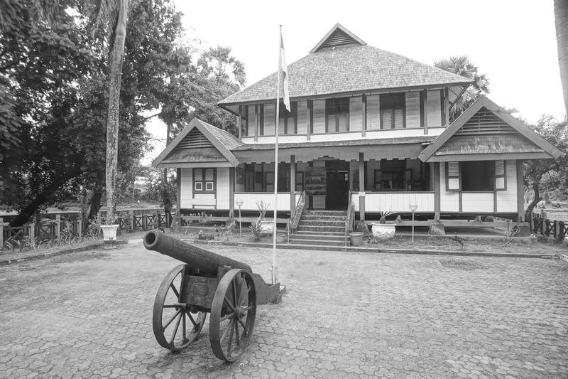 rumah adat di benteng somba opu makassar dengan meriam di depannyabe